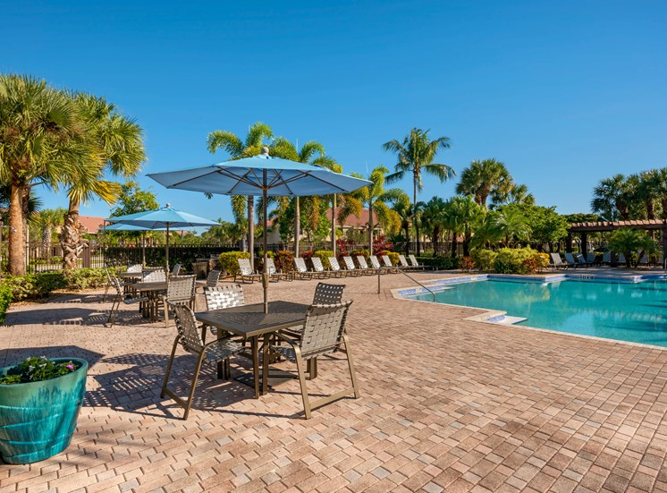 Swimming pool with sundeck, tables, chairs and umbrella