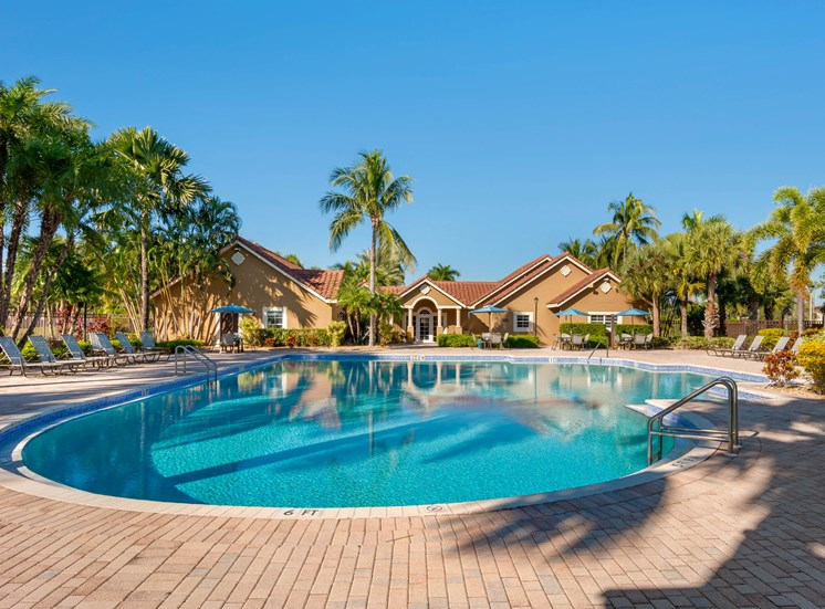 Swimming Pool with building exterior in the background and palm trees