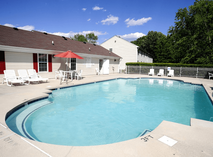 Swimming pool with lounge seating, picnic seating with umbrella shading, native landscaping surrounding the exterior