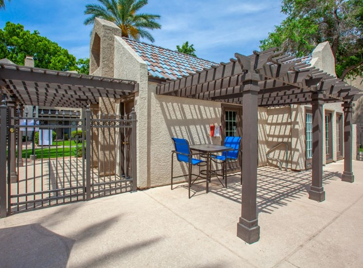 Pool Side Pergola with Bar Height  Patio Chairs and Table Next wo Building and Gate