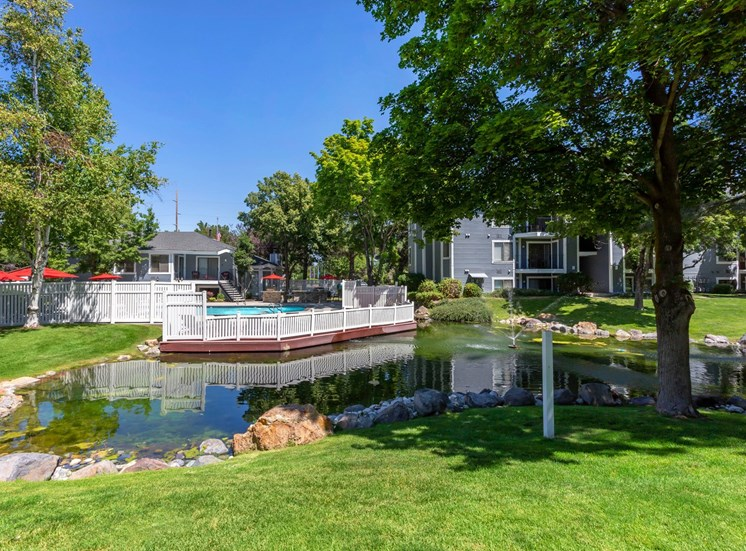 Poolside dock overlooking lake with apartment building in the background surrounded by native landscaping