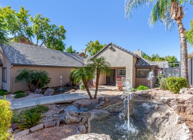 Building exterior with waterfall feature, palm trees, and a pond Clubhouse Exterior