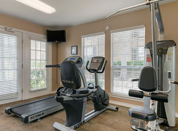 Fitness center with tv mounted on the wall in the corner, treadmill, spinning station, and a view of outside
