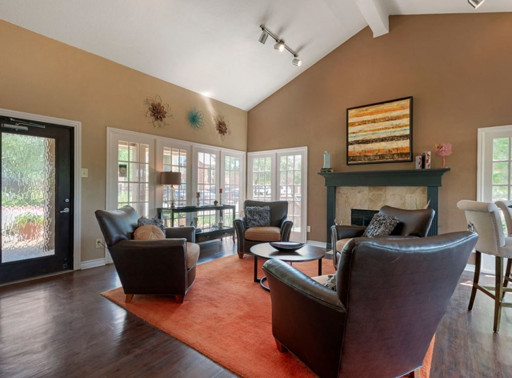Clubhouse interior with tan painted walls, white ceiling, orange rug, and recliners