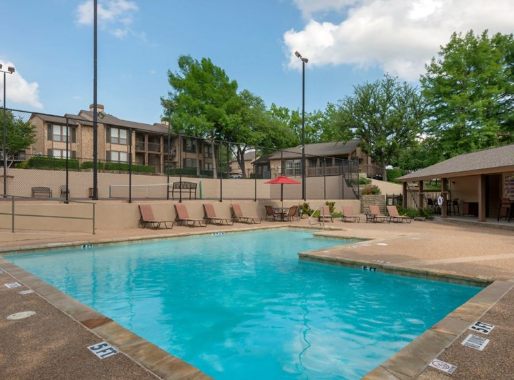 Swimming pool with tanning deck, tennis courts, and apartment exterior in the background