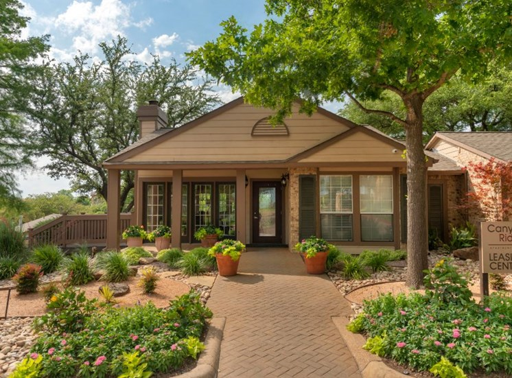 Leasing office with paved sidewalk, green grass, flowers, and large trees