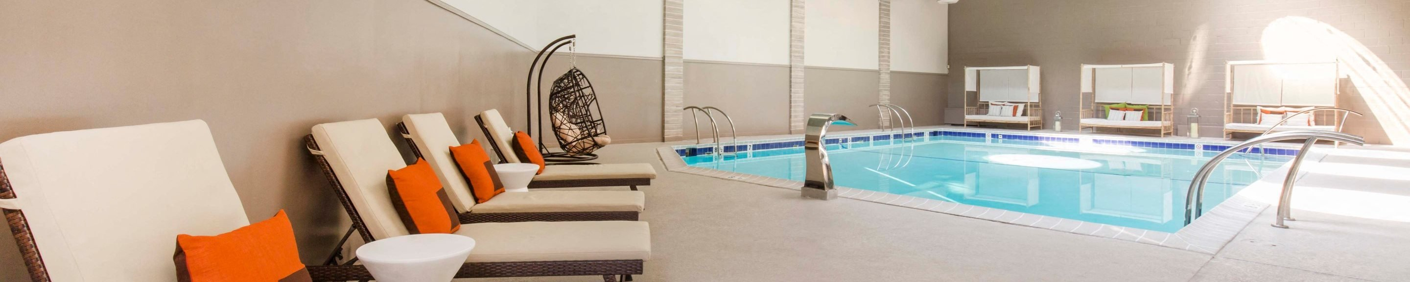 Indoor swimming pool with tan and white lounge chairs with orange accent pillows and natural sunlight coming through the ceiling