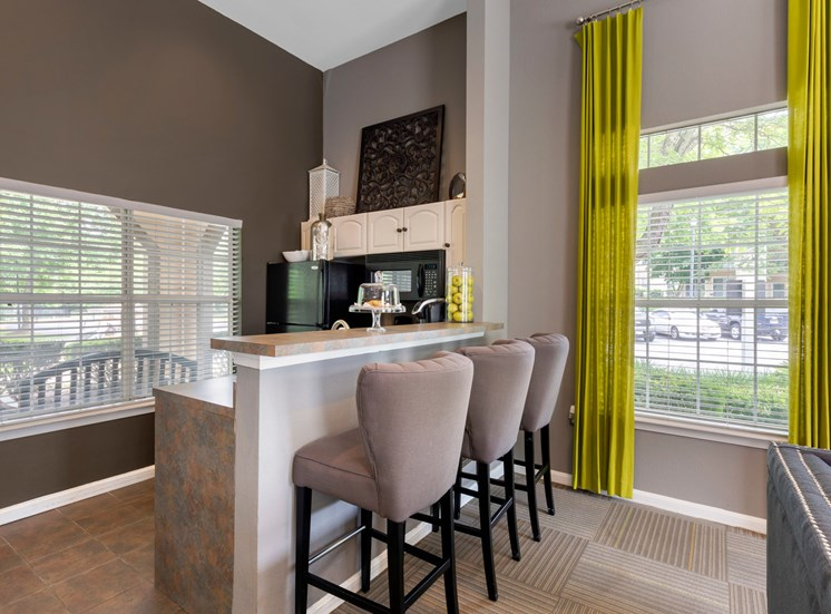 Clubhouse kitchen with 3 gray high top chairs, yellow curtains, tall bar top, black appliances and large open windows