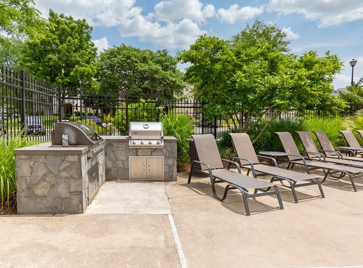 Sundeck with lounge chairs, and stone outdoor grilling area