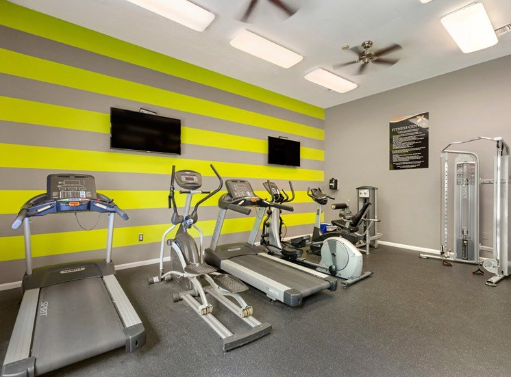 Fitness center with treadmills, ceiling fans and TVs.