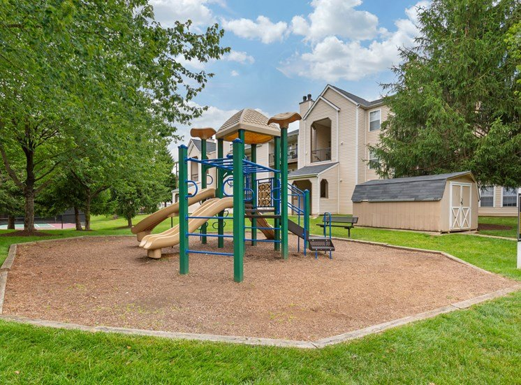 Playground on wood clips surrounded by building exteriors and trees