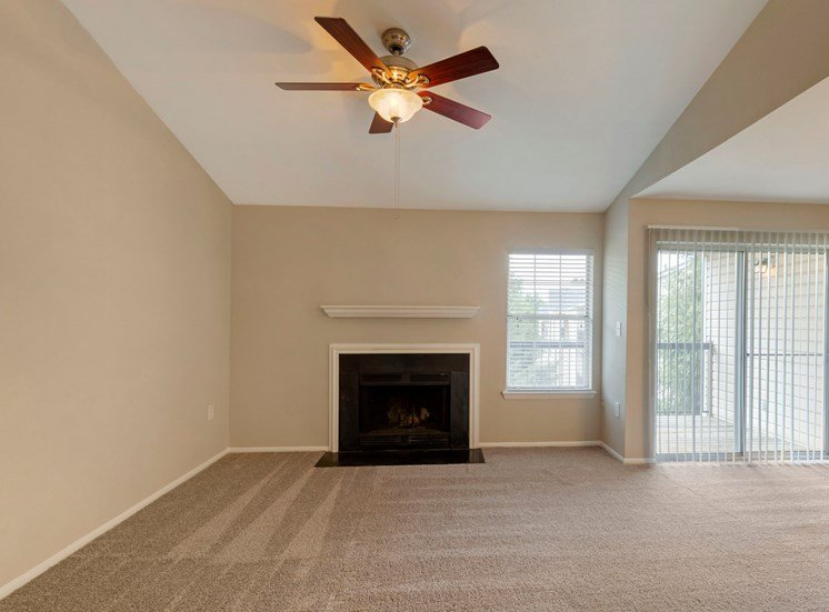 Carpeted living room with two-tone paint, ceiling fan, fireplace and sliding door to patio