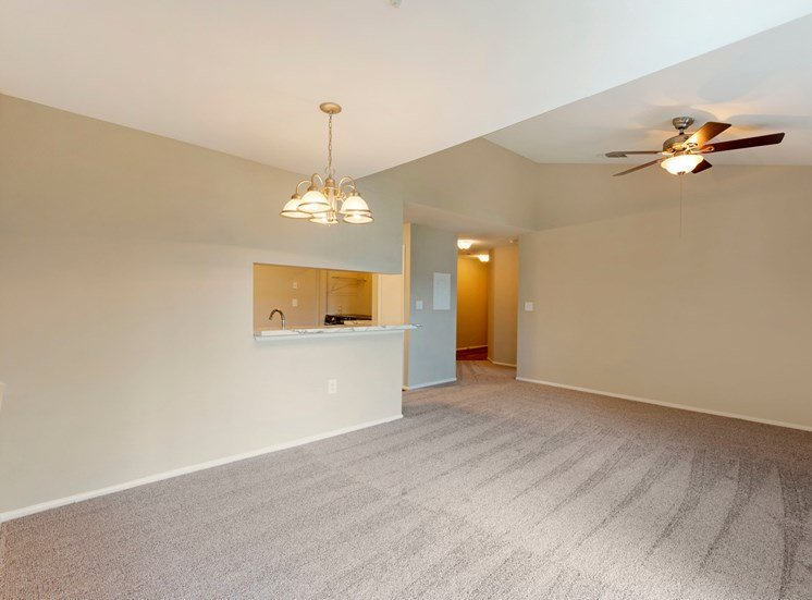 Carpeted living room and dining room with ceiling fan and pass through-bar to kitchen