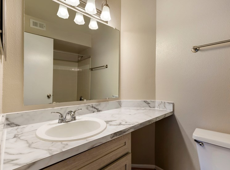 Bathroom with marble style countertops, brown cabinets, toilet and towel bar
