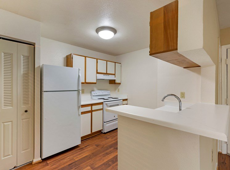 Classic Kitchen with brown and white cabinets, white appliances, hardwood-style flooring, and pantry