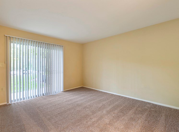 Carpeted bedroom with large sliding door to balcony