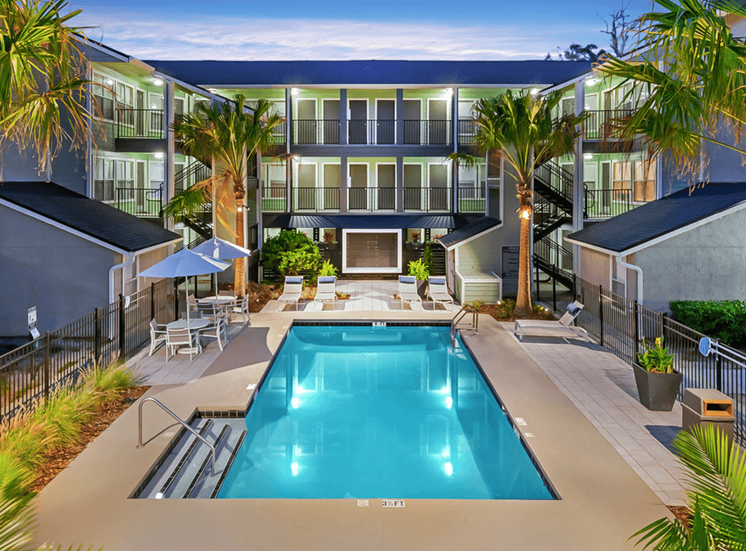 Swimming pool with lounge seating, palm trees, surrounded by native landscaping, and apartment building in the background