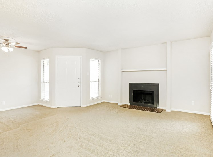 Living room with fireplace, carpet, white doors, and ceiling fan