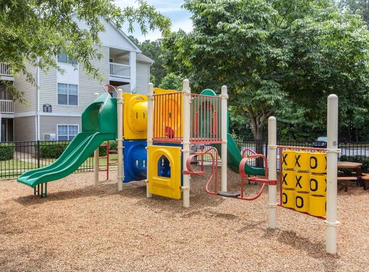 Playground on wood chips surrounded with trees and building exteriors