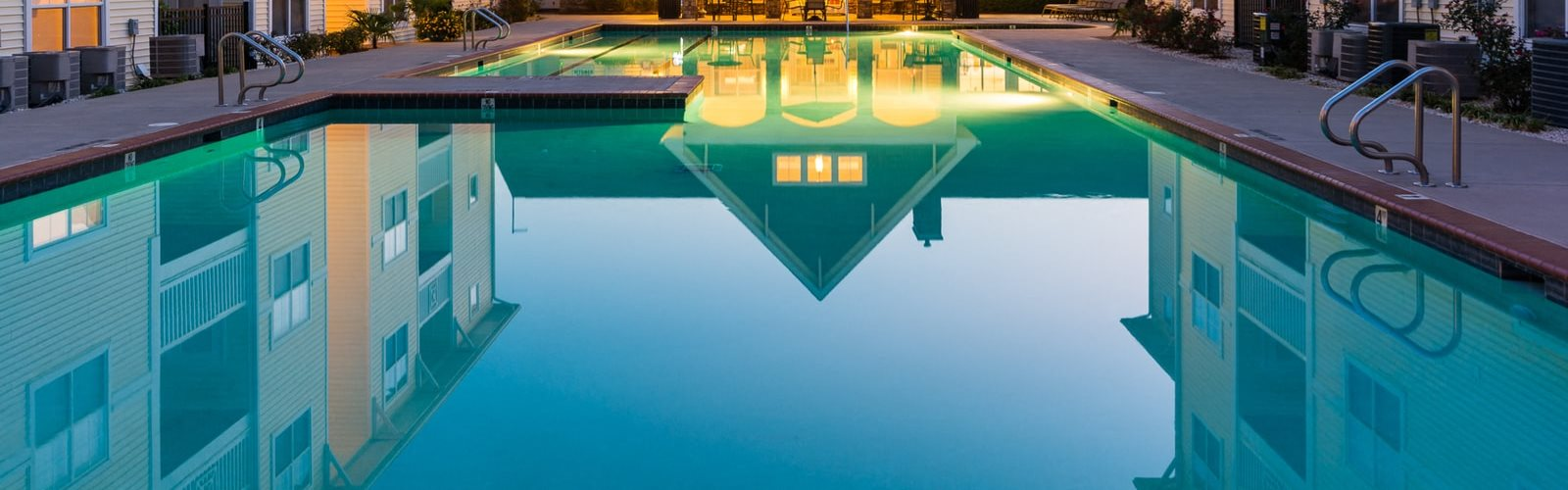 Swimming pool with sundeck surrounded by buildings and leasing office exterior