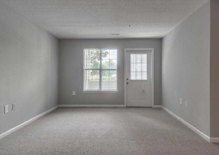 Empty living room with carpet, exterior door and window