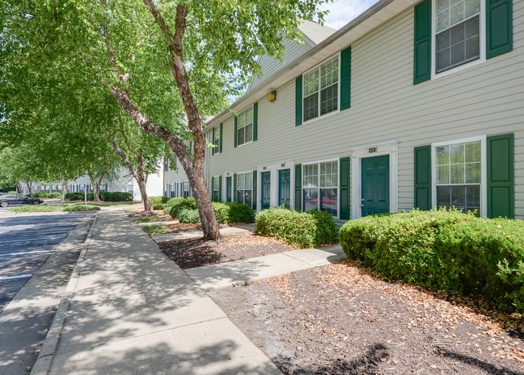 The apartment buildings have tan siding with green shutters and are two stories tall. There are sidewalks leading to the private entrances of each home