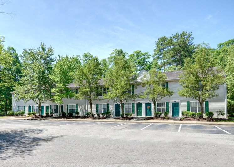 The apartment buildings have tan siding with green shutters and are two stories tall. There are sidewalks leading to the private entrances of each home.