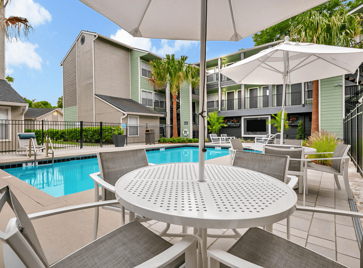 Poolside shaded picnic tables, lounge seating, swimming pool, and apartment building in the background
