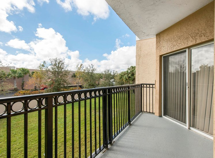 Balcony with Metal Railing , Sliding Glass Patio Door and View of Trees