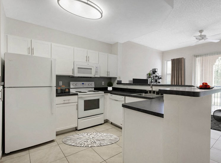 Fully Equipped Kitchen with White Appliances and Tile Flooring
