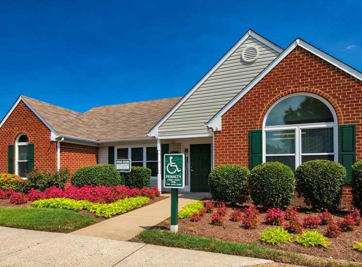 Leasing office exterior with large flower beds, bushes and the sidewalk