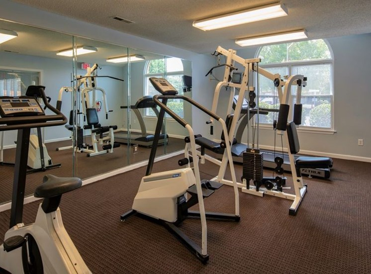 Fitness center with equipment and a mirrored wall.