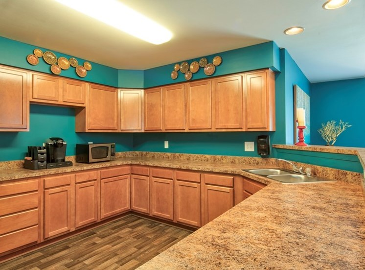 Clubhouse kitchen area with granite style countertops, cabinets, wood style flooring and white refrigerator