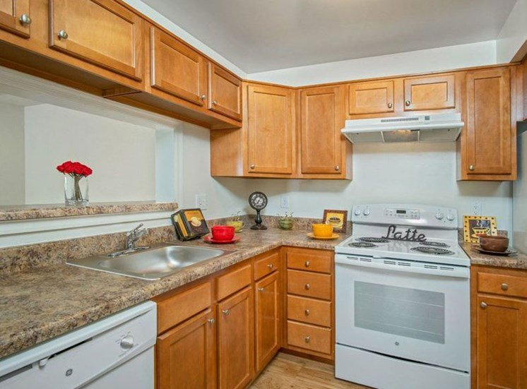 Kitchen with stove, dishwasher and refrigerator. Cabinets above all appliances and a breakfast bar