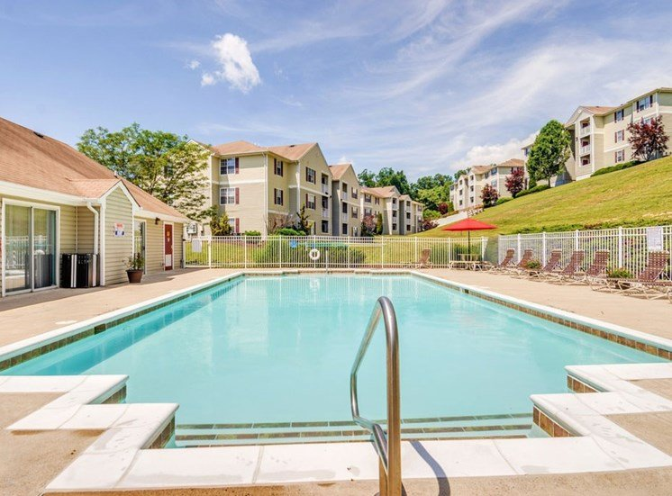 Swimming pool with lounge chairs alongside the pool. Tress and apartment buildings in the background