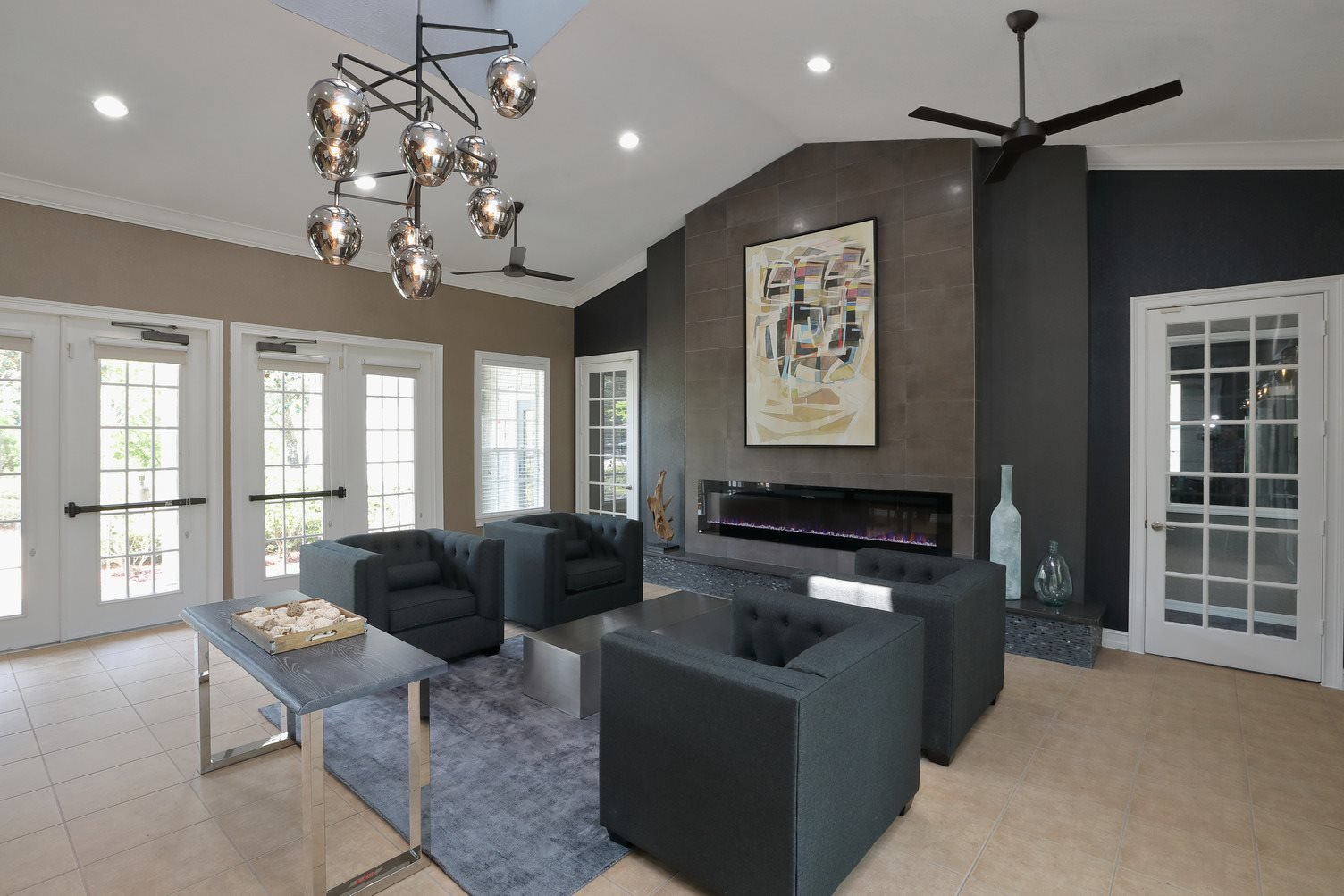 The Resident Lounge is a big room with a contemporary design. The far wall shows a large painting artwork above a fireplace. Four dark chairs are sat around a small table in front of french doors.