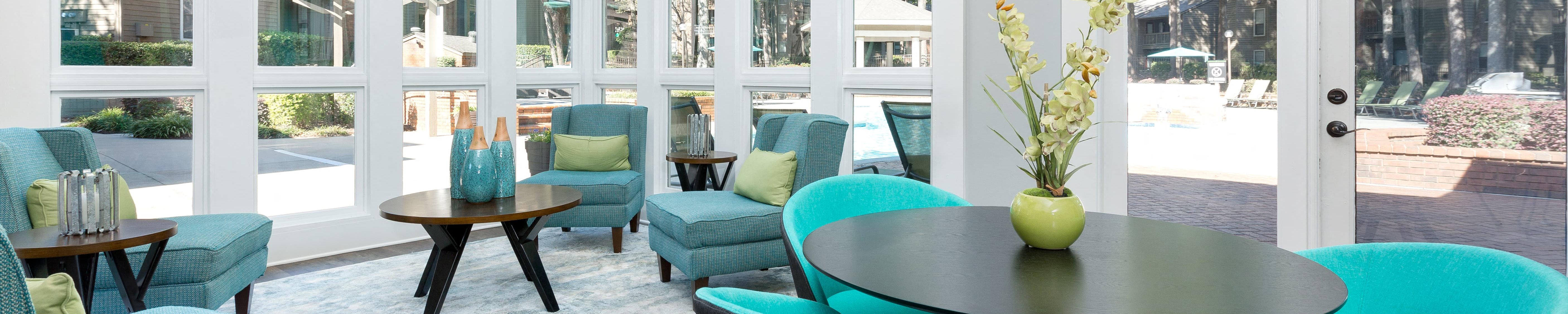 Clubhouse interior with a teal and lime color scheme, two wooden tables, a wall of windows, and a light blue and white rug