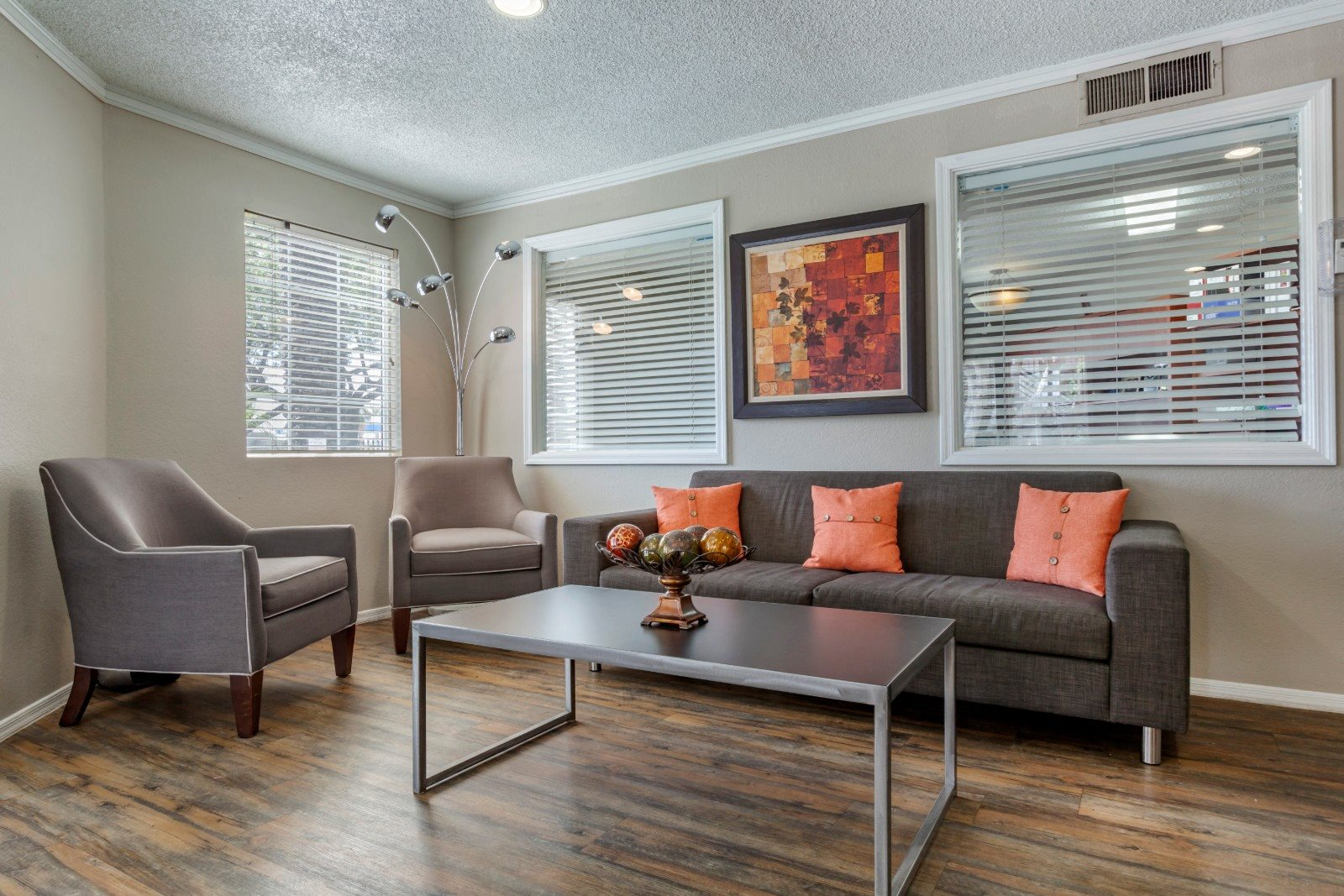 Clubhouse Seating Area with Grey Couch with Orange Pillows and Armchairs with Coffee Table in Front of  WIndows