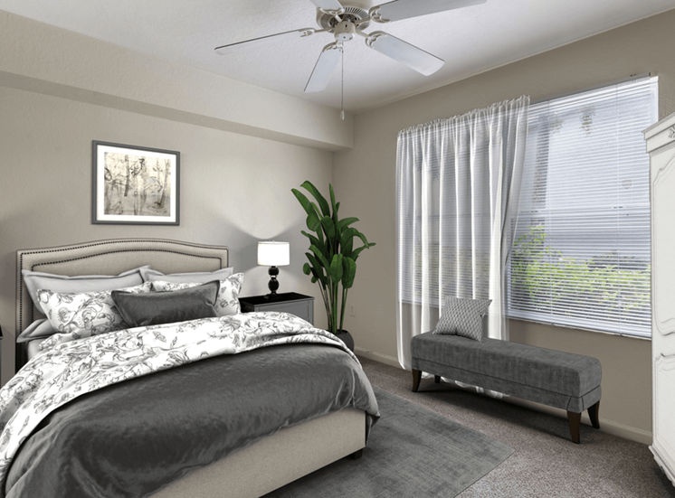 Virtually staged bedroom with tan carpeted flooring, arge window with white blinds and a white multi-speed ceiling fan