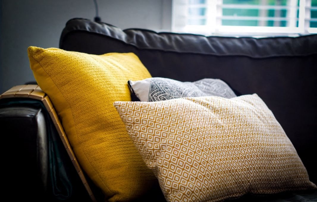 Yellow and gray throw pillows on a a dark gray couch