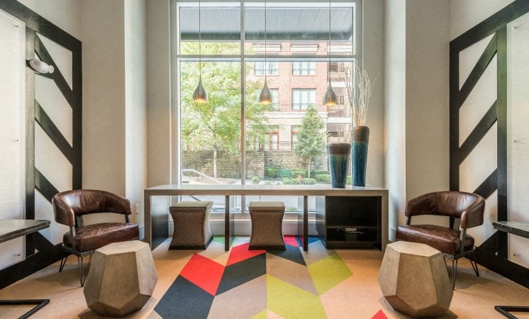 Clubhouse Seating Area with Colorful Area Rug with Stools and Long Desk in Front of a Window