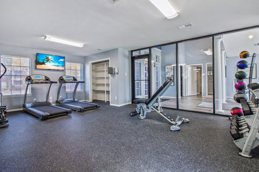 Fitness Center with Cardio Equipment facing the wall with a mounted television.