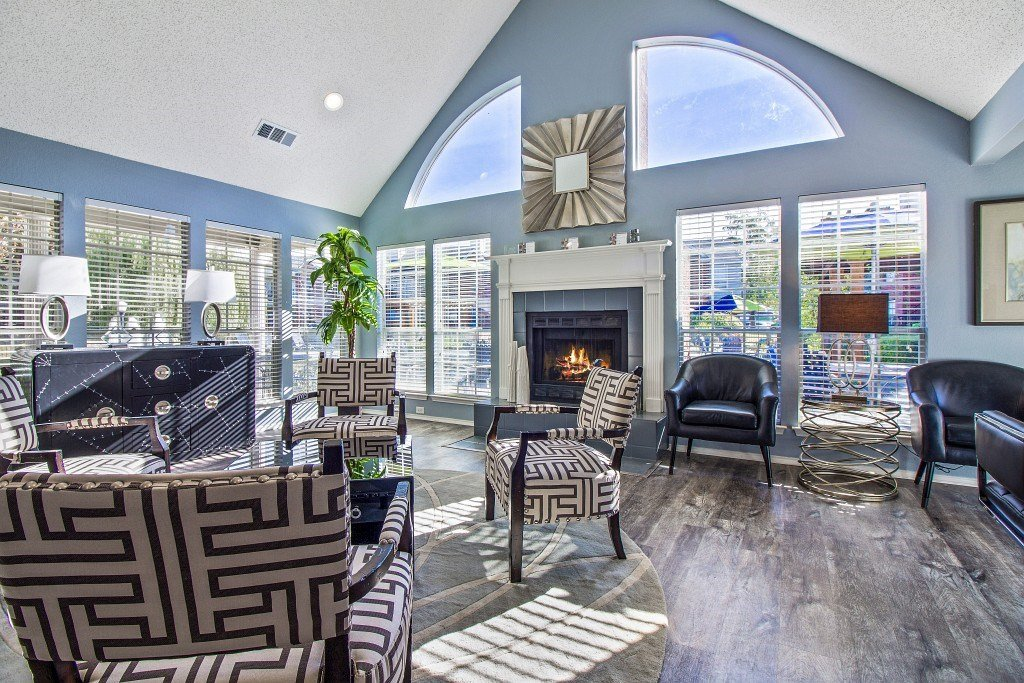 Clubhouse lounge area with a fire place it the background. arm chairs and coffee tables