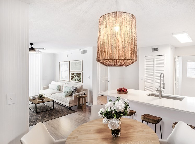 Open Layout Model with Kitchen Breakfast Bar, Stainless Steel Appliances, Bar Stools, Dining Table and Chairs and Fuller Furnished Living Room in The Background