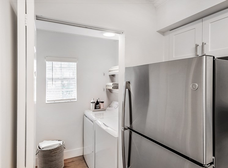 Stainless Steel Fridge Next to Utility Closet with Full-sized Washer and Dryer