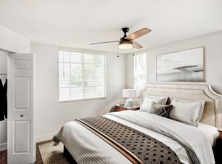 Model Bedroom with Bed Under Wall Art, Nightstand Next to Open Walk In Closet