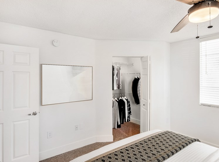 Model Bedroom with Bed Under Ceiling Fan, Wall Art Next to Open Walk In Closet