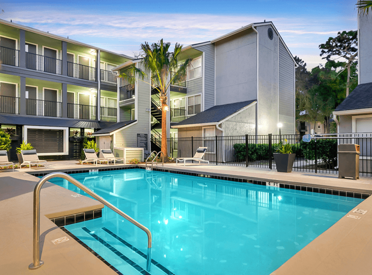 Swimming pool with lounge seating, palm tree, and apartment building exterior in the background