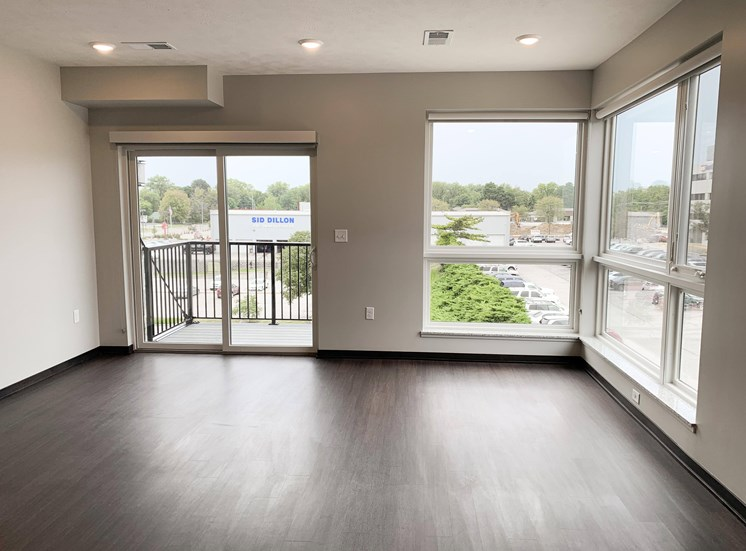 Living room view through corner floor to ceiling windows and sliding door that look out onto north Lincoln, Nebraska