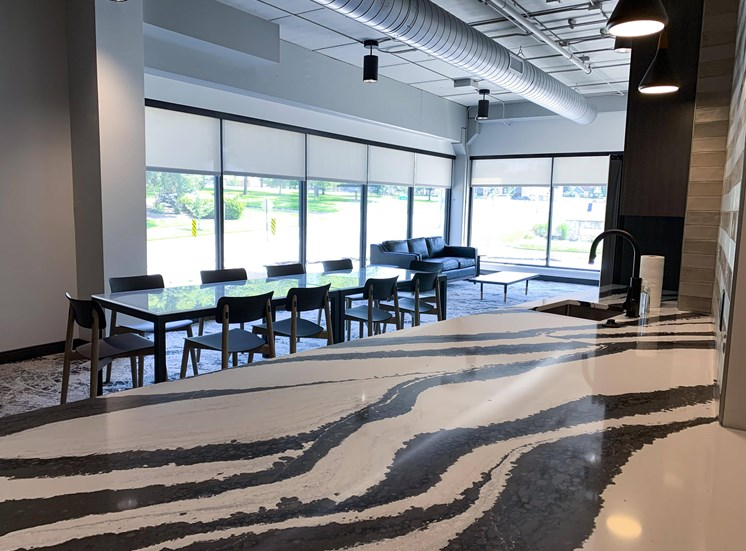 community room with lounge seating and kitchen at Haven at Uptown in Lincoln, NE